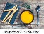 Small photo of Top view of a carrot soup and pumpkin on a wooden table with the accompanying bread sticks on a lava stone tile and a metal spoon