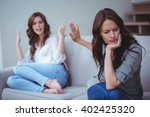 Small photo of Two female friends sitting on sofa and arguing with each other