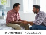 adult son comforting father... | Shutterstock . vector #402621109