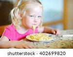 cute funny little girl eating... | Shutterstock . vector #402699820