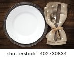 Small photo of Table place setting with vintage silverware and plate on rustic wooden background