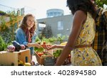 Small photo of Friendly woman tending an organic vegetable stall at a farmer's market and selling fresh vegetables from the rooftop garden