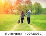 Stock photo happy family with dog walking on the rural dirt road little girl sitting on dad s shoulder 402920080