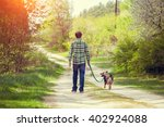 Stock photo young man walking with a dog in the village 402924088