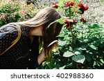 Stock photo beautiful young girl in polka dot shirt in botanic garden with roses 402988360