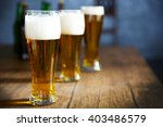 three glasses of light beer on... | Shutterstock . vector #403486579