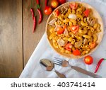 Small photo of Fried macaroni with pork and vegetable in tomato sauce in plate placed on a wooden table
