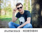 young man relaxing in the park... | Shutterstock . vector #403854844