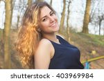 smiling curly girl in the park... | Shutterstock . vector #403969984