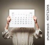 woman is holding july calendar... | Shutterstock . vector #404712646