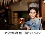 Young Woman Drinking Beer In A...