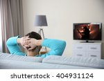 young handsome man watching tv... | Shutterstock . vector #404931124
