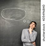 Small photo of Young inspirited man standing nearly chalkboard background with speech bubble and dreaming