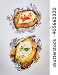 Small photo of Two barbecued baked potatoes in tin foil topped with sour cream and garnished with chopped chives and peppers viewed from overhead still in the foil wrapping