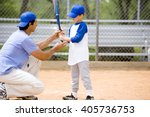 Small photo of Young boy being shown how to bat in baseball