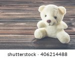 White Teddy Bear On A Wooden...