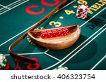 Small photo of Full set of 5 dice in a wooden bowl next to the stick on a craps table with stacks of casino chip around