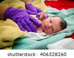 Stock photo a newborn baby born at home gets his vitals taken as he looks at the camera the midwife s 406328260