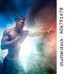 Small photo of Muscular, aggressive fighter punching in smoke.