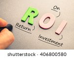 Small photo of Hand writing definition of ROI wood letters abbreviation