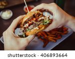 Man Holds Burger With Hands An...