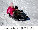 Boy And Girl Riding Down A Sno...