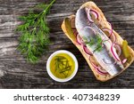 Stock photo sandwich with herring fillets onion pickled cucumber and dill on parchment paper on an oval dish 407348239