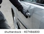 Close up on car thief hand pulling the handle of a car. Car thief, car theft concept - stock photo