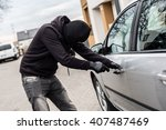 The man dressed in black with a balaclava on his head trying to break into the car. He uses a screwdriver. Car thief, car theft concept - stock photo