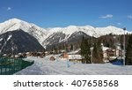 Ski resort in the Caucasus mountains, snow slope, cottage village, snowy peaks and blue sky - stock photo