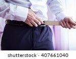 businessman putting on a belt ... | Shutterstock . vector #407661040