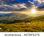 white sharp boulders on the grassy meadow on the edge of hillside in  high mountain range in evening light - stock photo