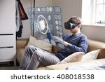 Stock photo man sitting on sofa at home wearing virtual reality headset 408018538