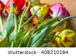 Small photo of Bouquet of colorful yellow and red tulips with greenery lying in disarray on a wooden table