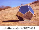 Small photo of Space mirror polyhedron on red planet on blue sky background. Unusual surrounded by usual. Modern concept art installation on nature. Reflection of habitual in versatile object. Beautiful futuristic