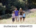 A Family Standing In A Field