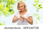 Small photo of people, healthcare, dermatology, allergy and health problem concept - unhappy woman suffering from hand inch over green natural background