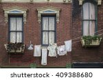 Stock photo old style residence brick building with cloths hanging out the window 409388680