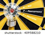 Small photo of KPI acronym of key performance indicator with idea bulb lamp target on dartboard background, Top view, Business concept