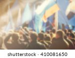 Small photo of Blur unrecognizable crowd at political meeting, cheering audience looking at the stage and supporting political party, defocussed retro toned image with lens flare.