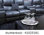 black executive leather home theater chairs with wine glasses on tray on black table - stock photo