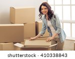 Stock photo attractive young woman is moving standing among cardboard boxes looking at camera and smiling 410338843