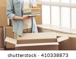 Stock photo cropped image of attractive young woman moving packing books in cardboard box looking at camera 410338873