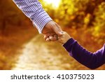 the parent holds the hand of a... | Shutterstock . vector #410375023