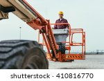 Small photo of Operator In Safety Helmet and red square shirt controlling Straight Boom Lift