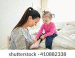 mother dressing her daughter in ... | Shutterstock . vector #410882338