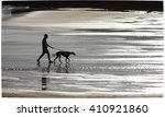 Stock photo silhouette of a man with a dog on a leash 410921860