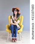 trendy woman with hat sitting... | Shutterstock . vector #411107683