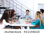young colleagues sitting at the ... | Shutterstock . vector #411144610