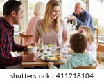 family enjoying meal in... | Shutterstock . vector #411218104